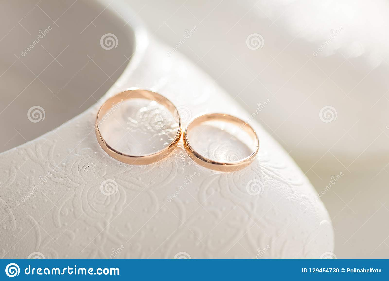 Two Gold Wedding Rings On The Background Of The Bride S Shoes Stock