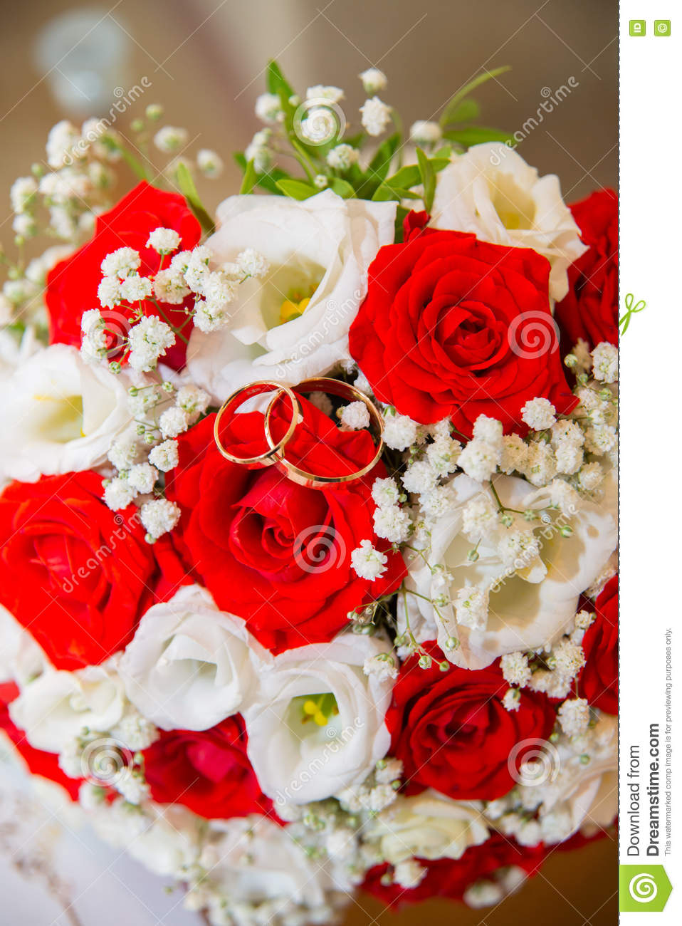 Two Gold Wedding Rings Lie On A Bouquet Of Red And White Roses ...