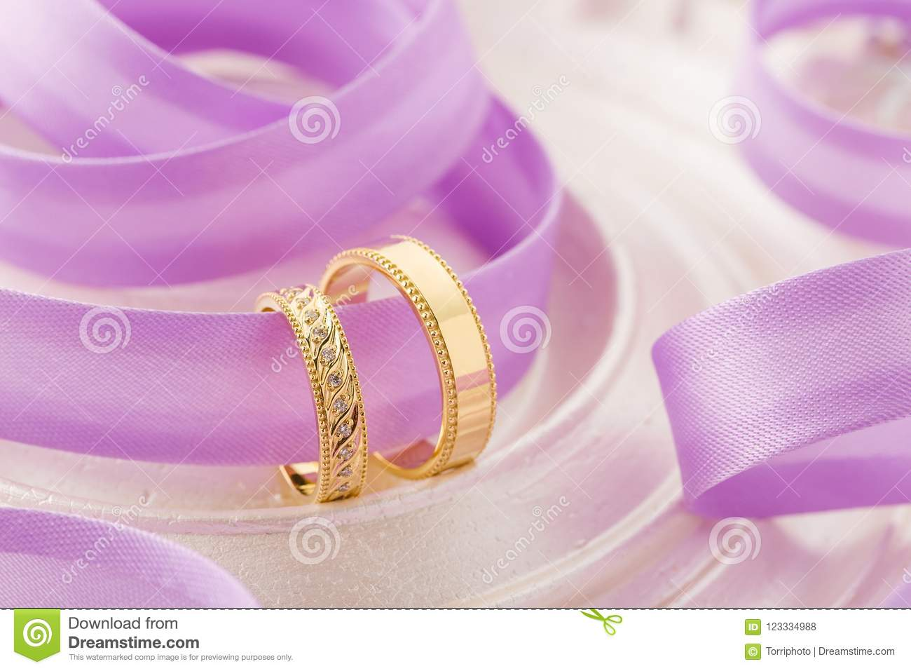 Two Gold Wedding Rings On Purple Ribbon Background Stock Photo ...