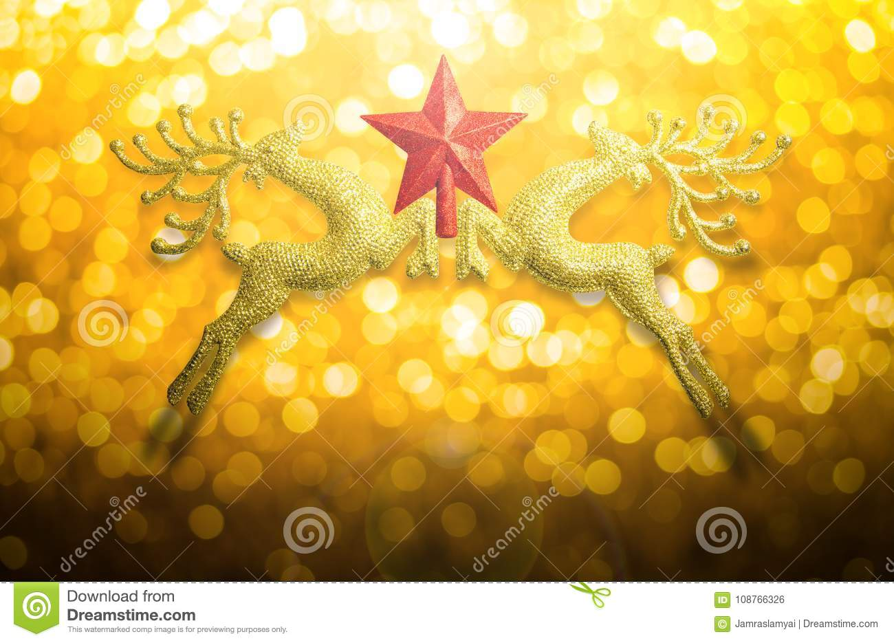 Two golden reindeer with red star on circular bokeh yellow gold background and copy space