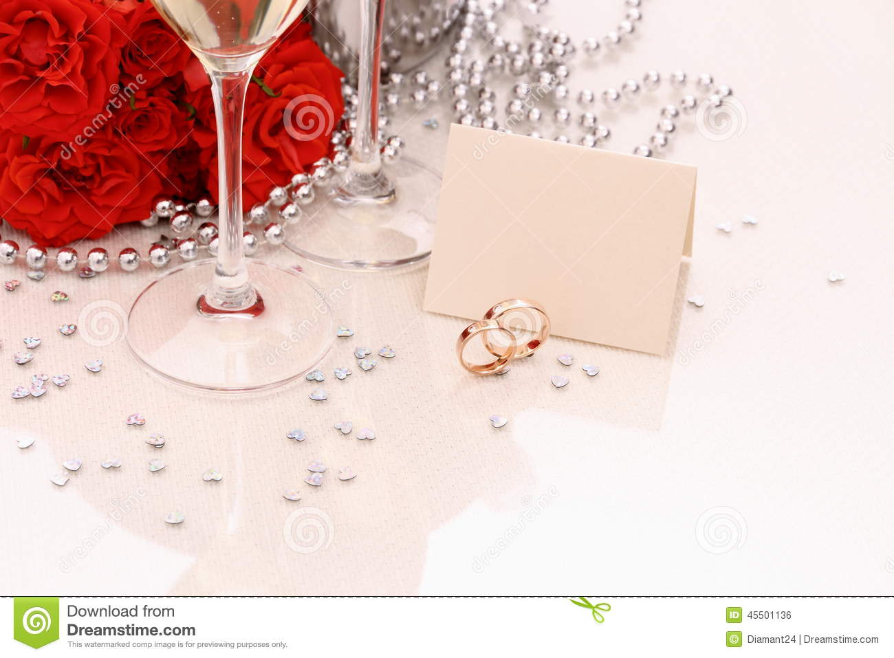 Two golden wedding rings with card, champagne glasses