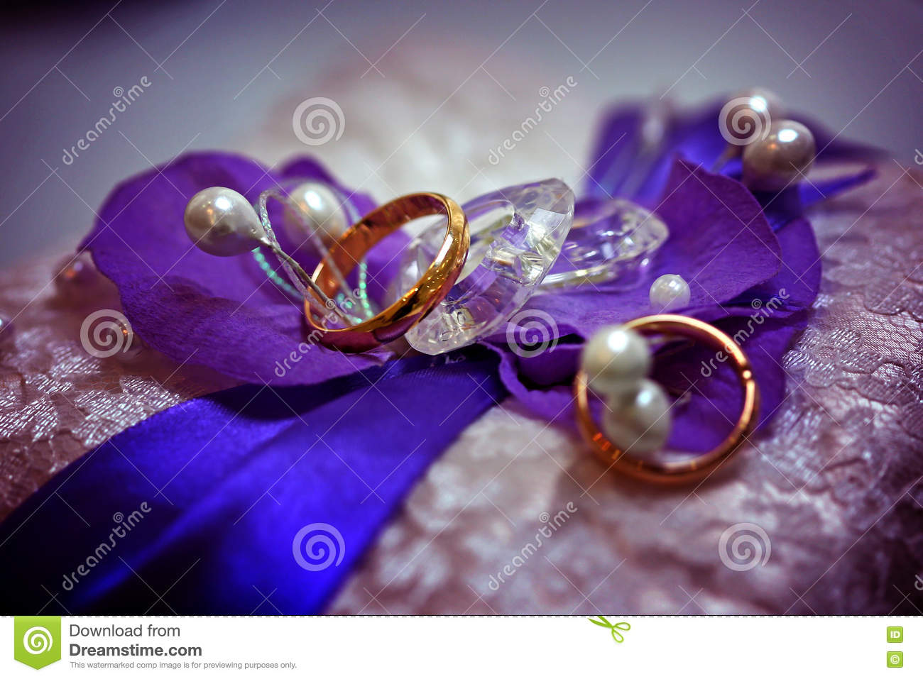 two golden wedding rings on purple background with stones
