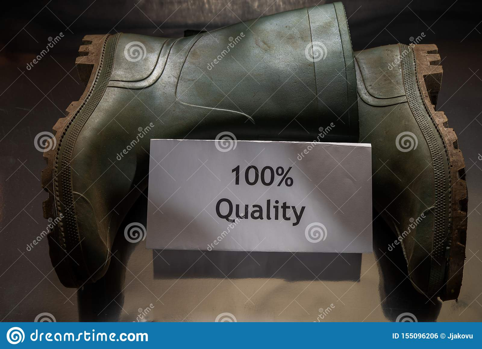 Two green rubber boots with note `100  Quality` are on the dark background/table. World Quality Day.