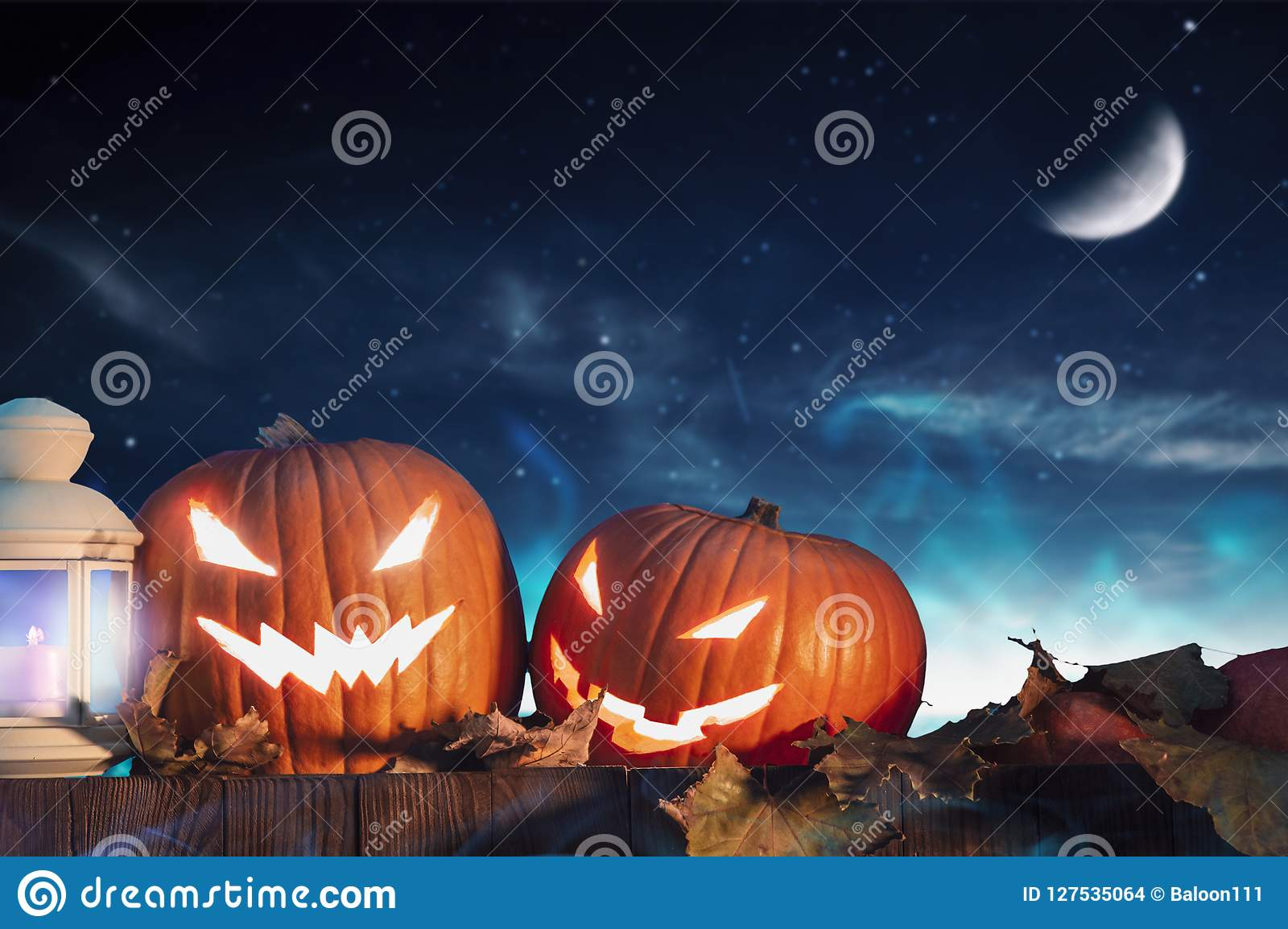 Two halloween pumpkins on fence with starry sky