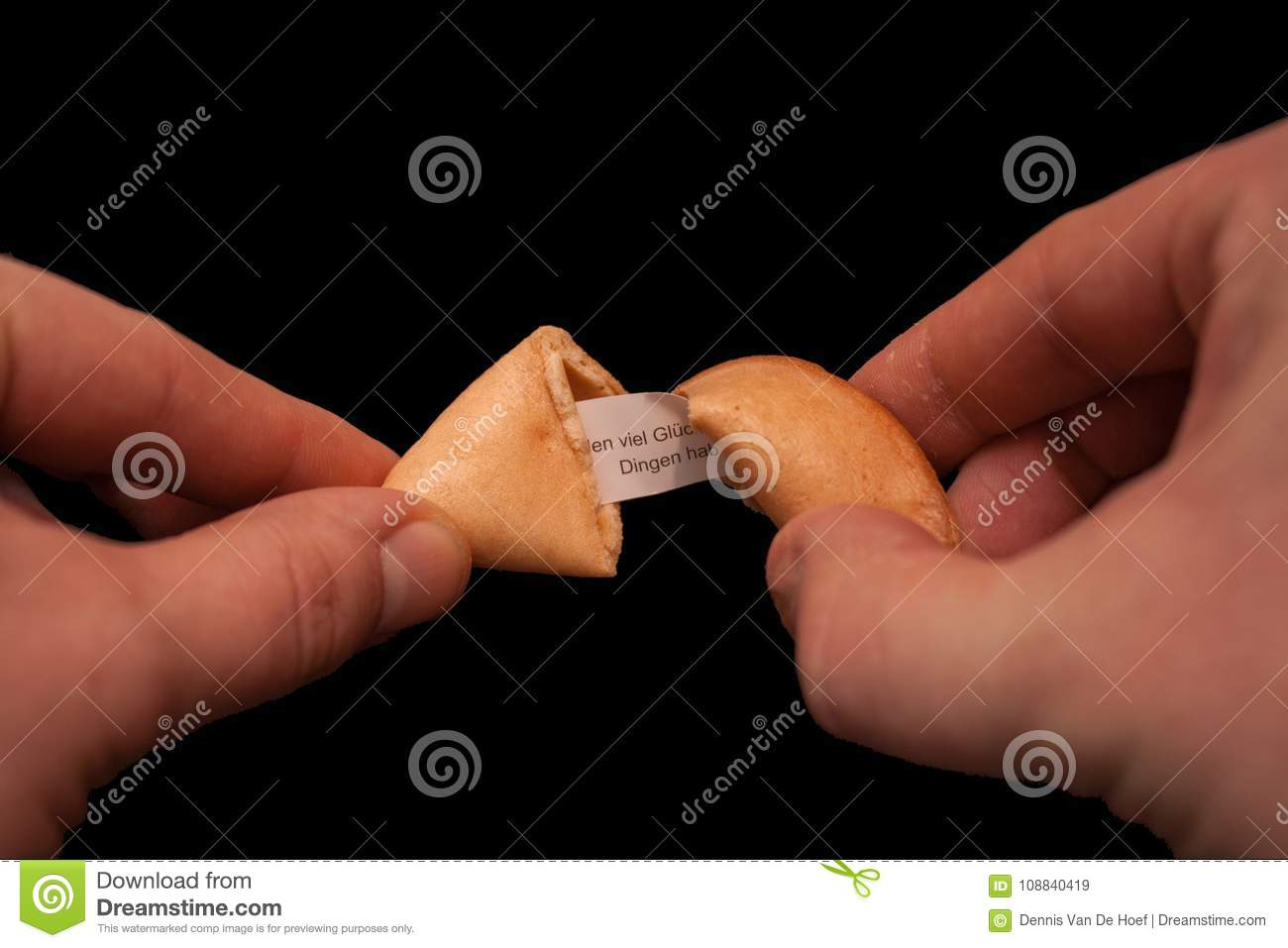 Two hands cracking a fortune cookie.