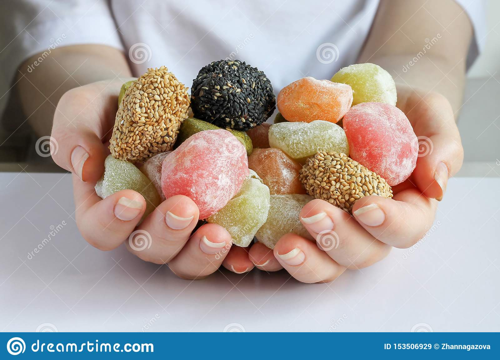 Many soft multi-colored candies in two hands