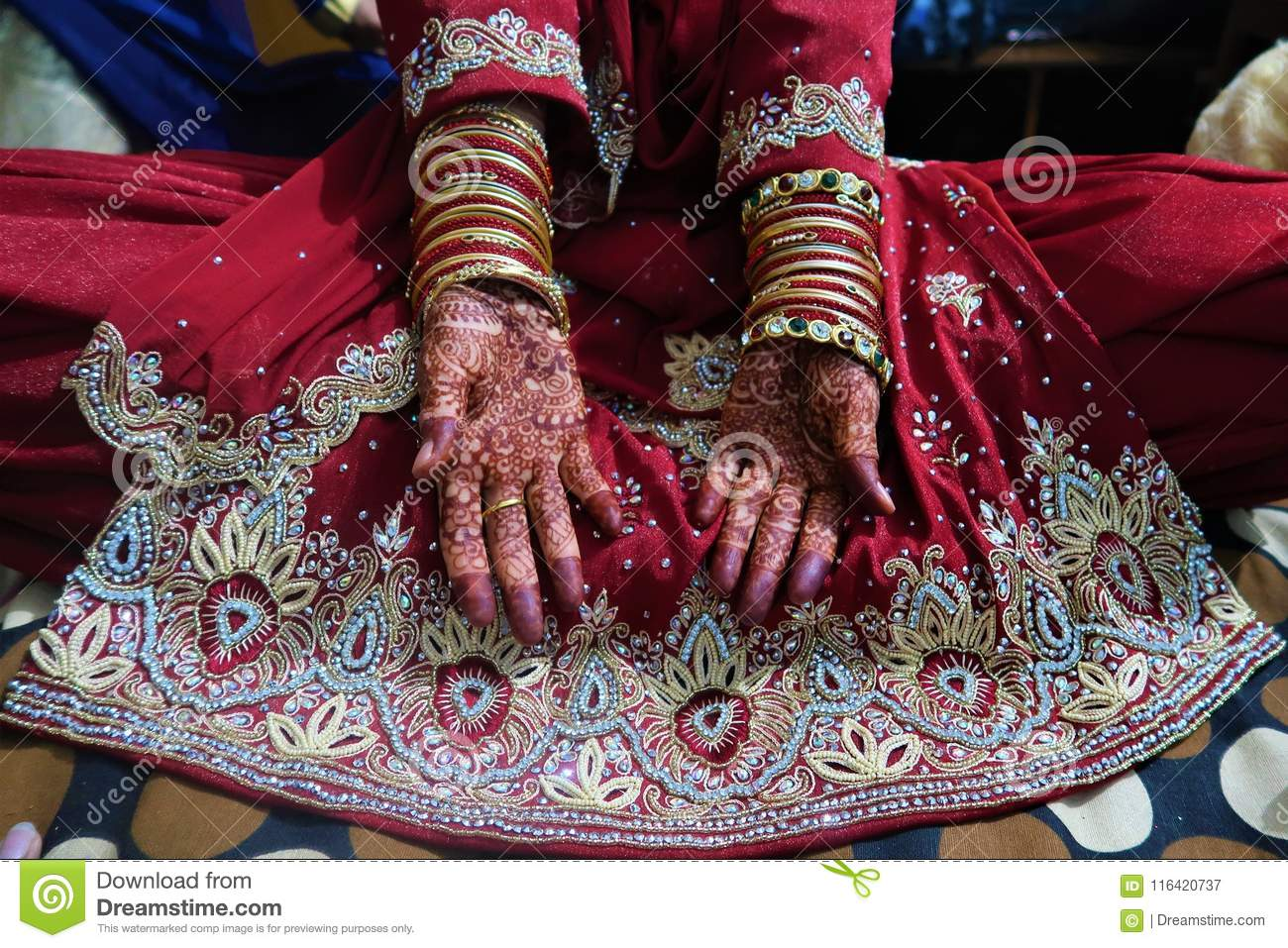 Two Hands Of Indian Bride With Henna Mehndi And Bangles And Red