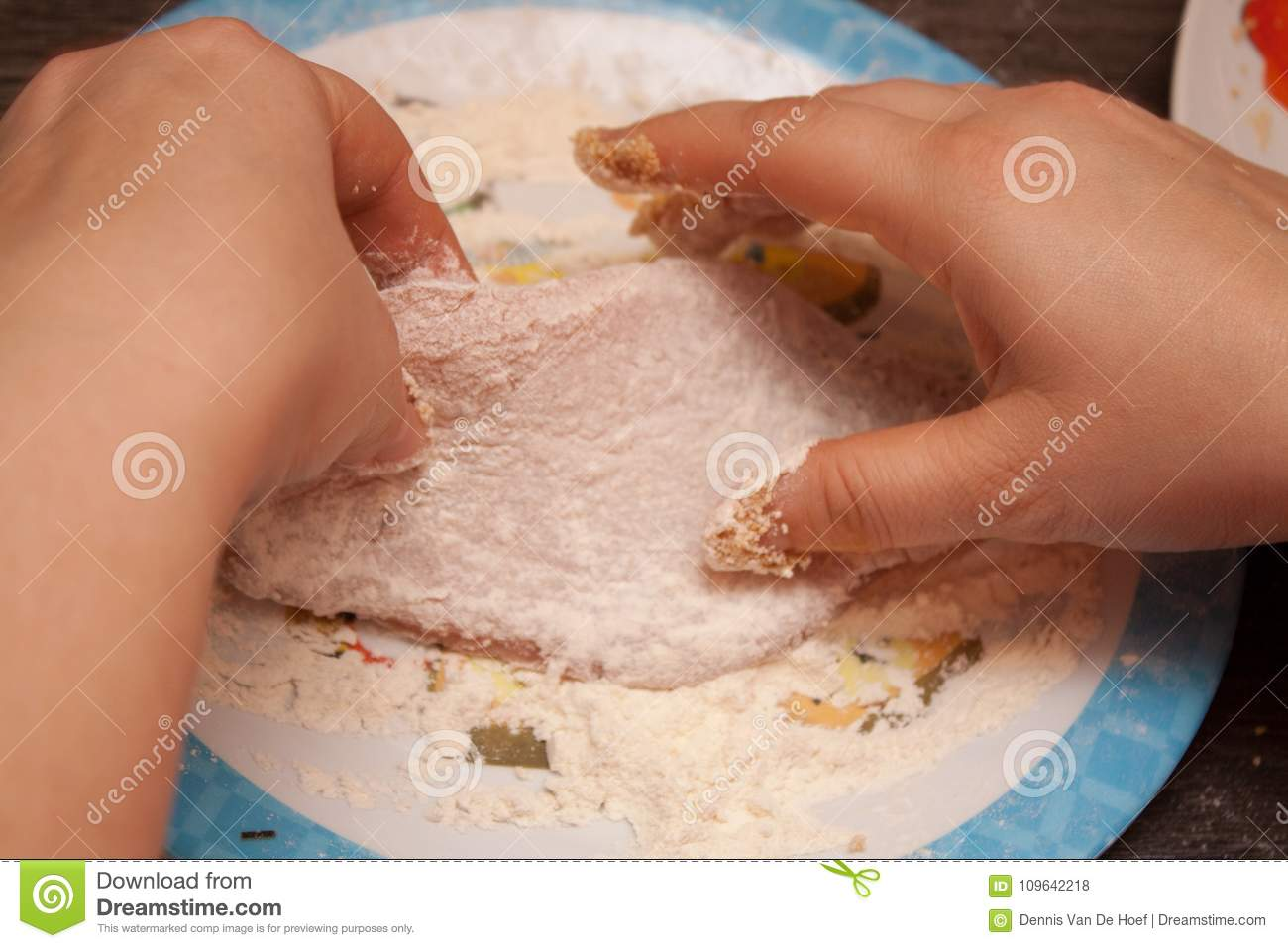 Two hands putting flour on meat to making a wiener schnitzel.