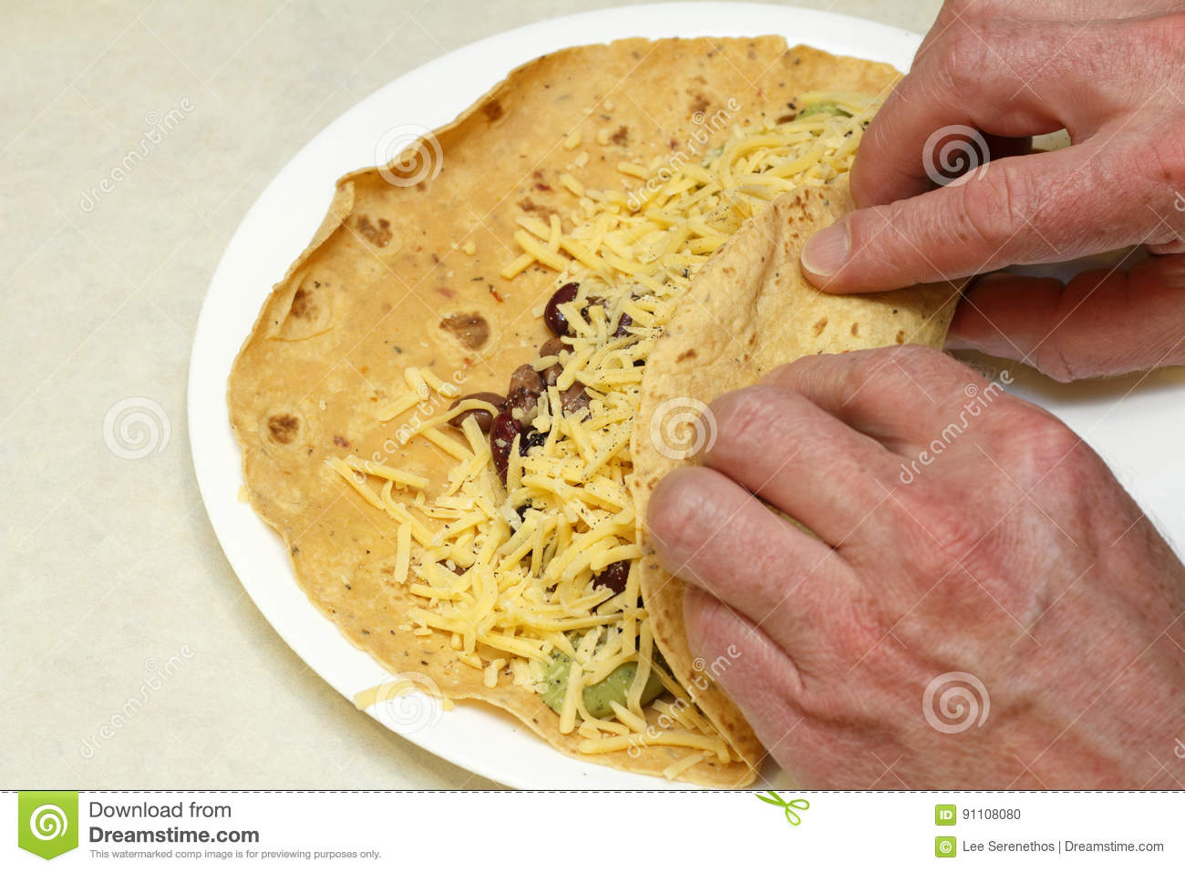 Two Hands Rolling a Vegetarian Burrito