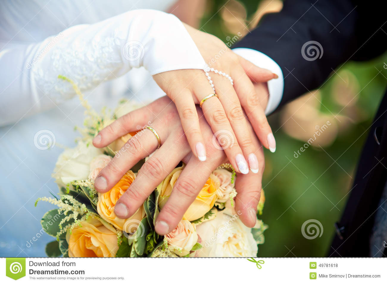 two hands with wedding rings on bouquet of bride stock