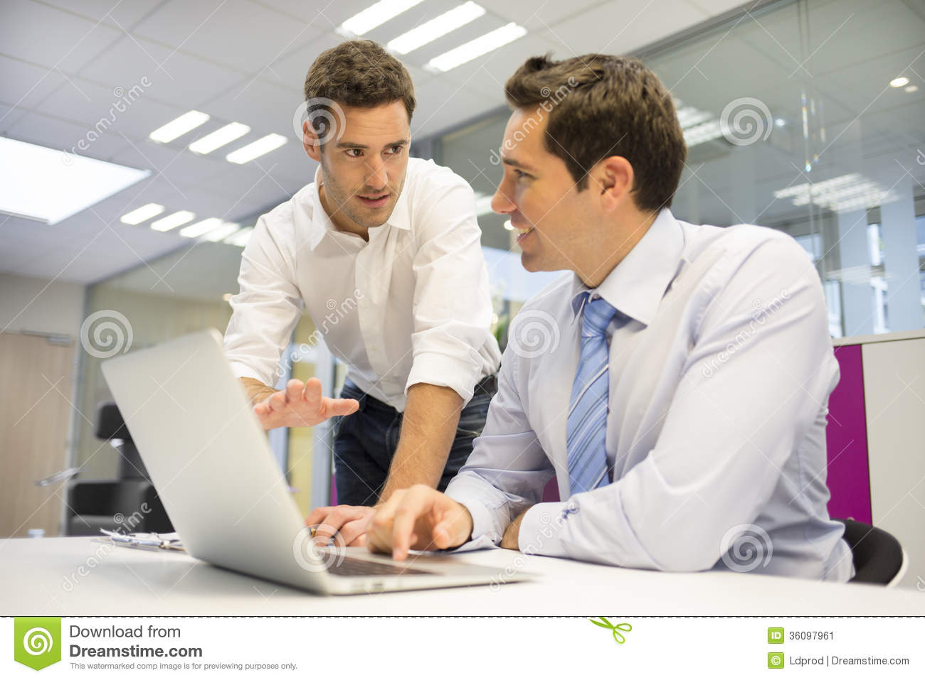 Two Handsome Businessmen Working Together On A Laptop In ...