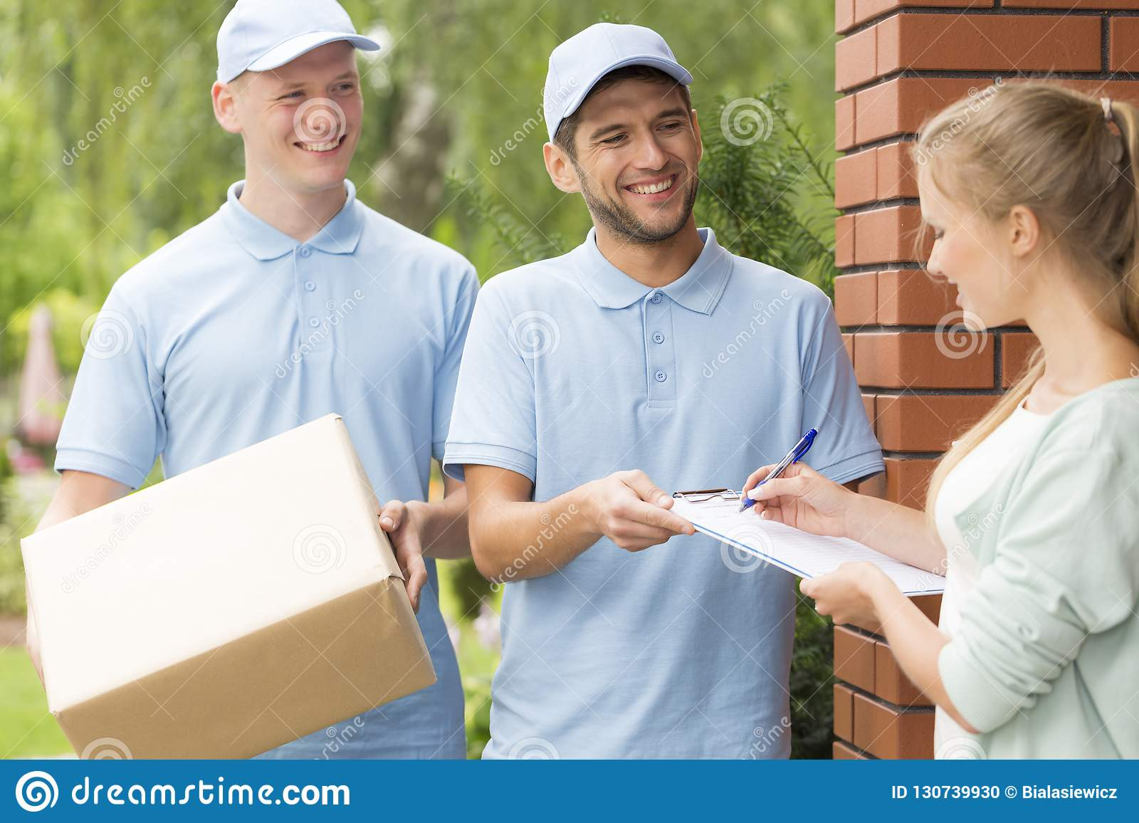Handsome couriers in blue uniforms delivering a parcel to a young pretty woman