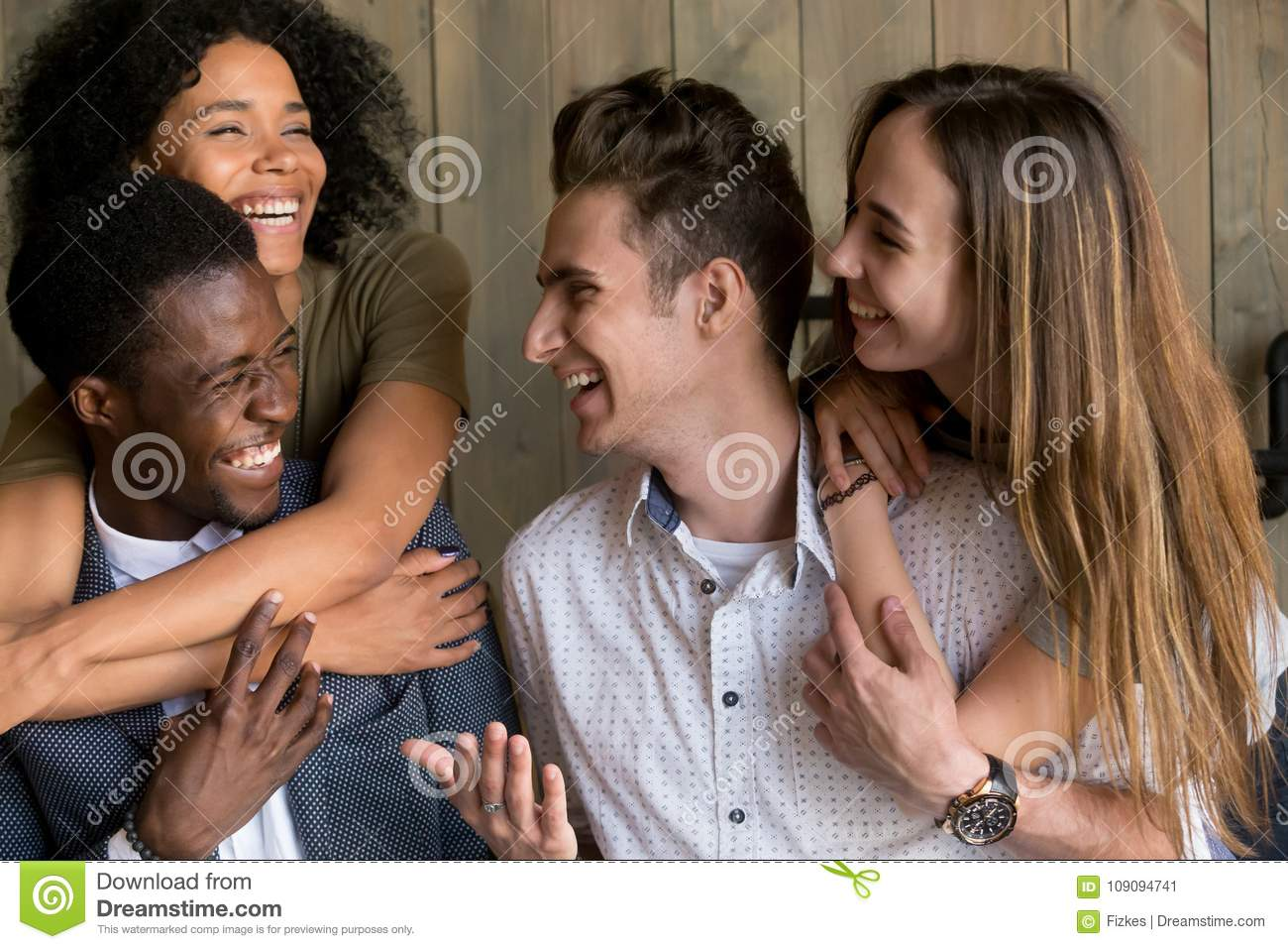 Two happy african and caucasian couples embracing having fun tog