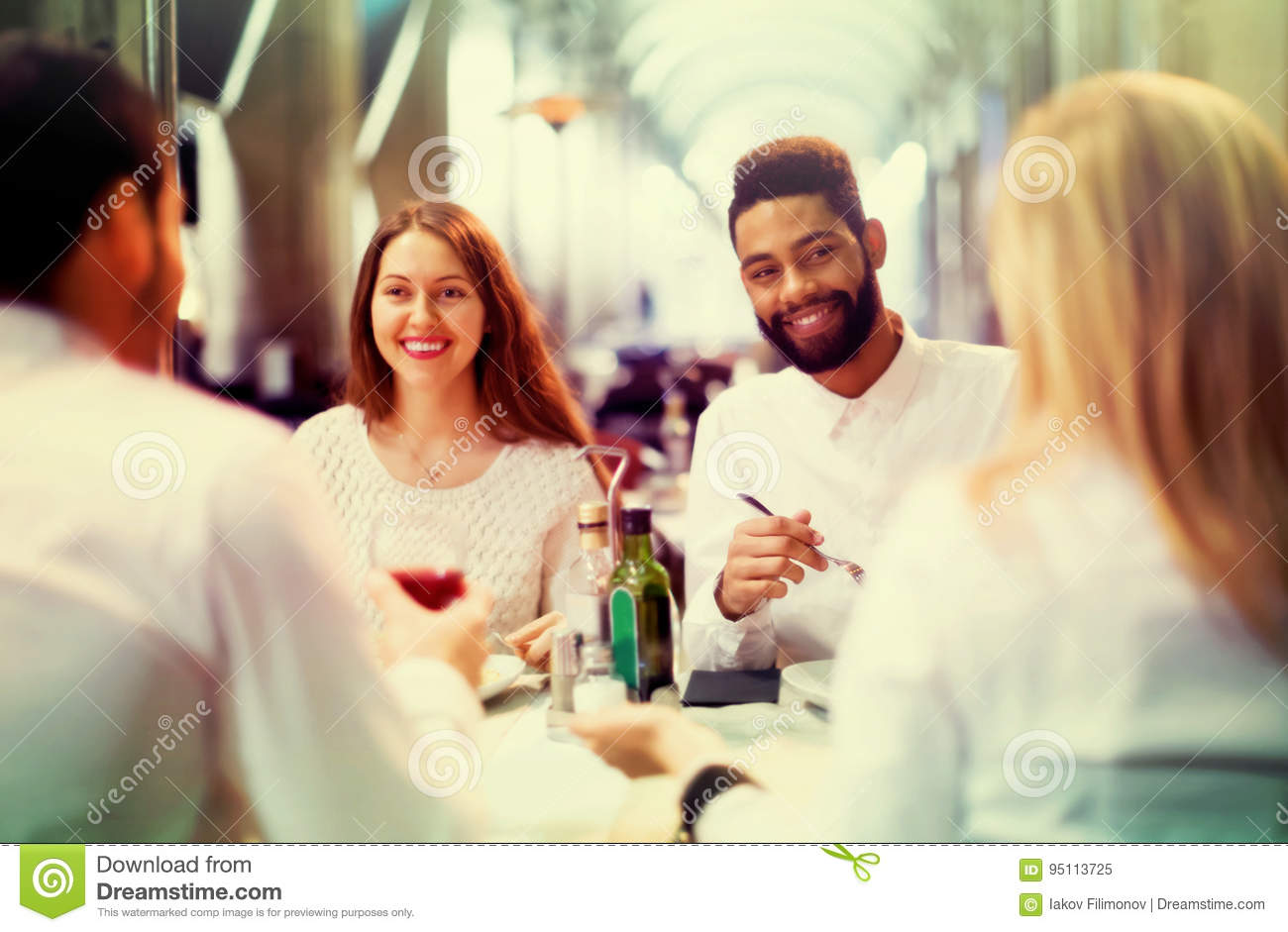 Two happy couples sitting at outdoor restaurant