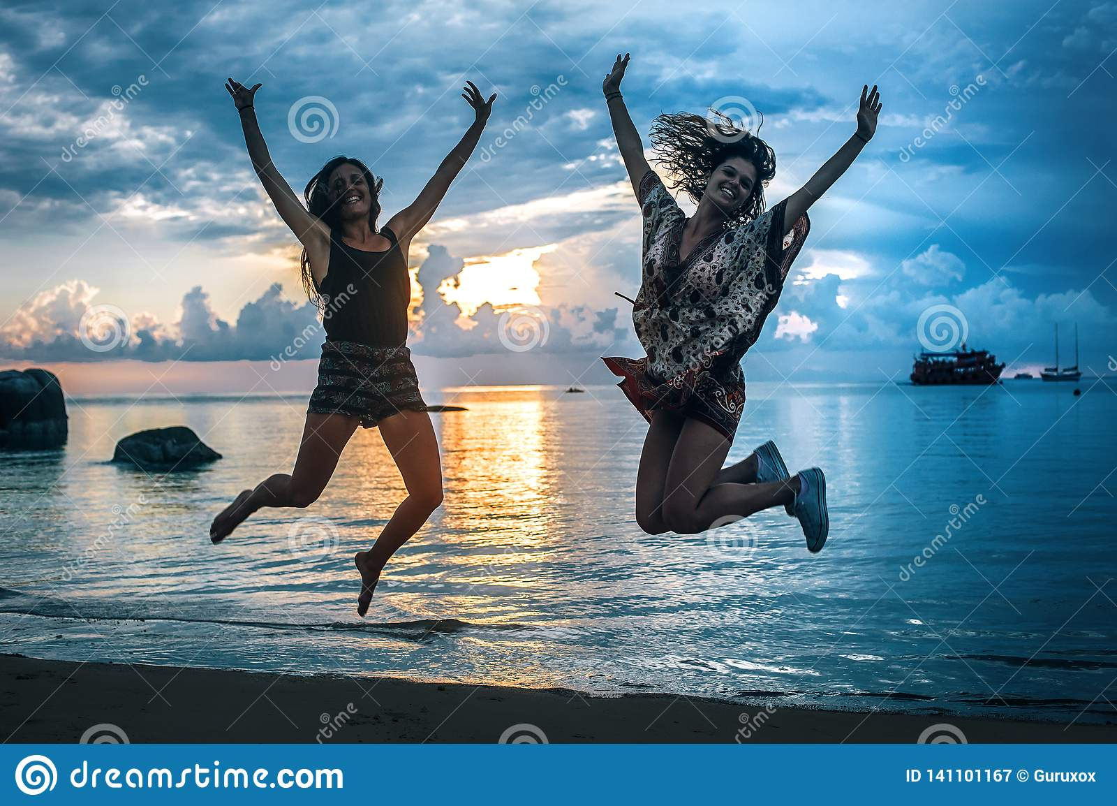 Two happy girls jumping at sunset on tropical beach