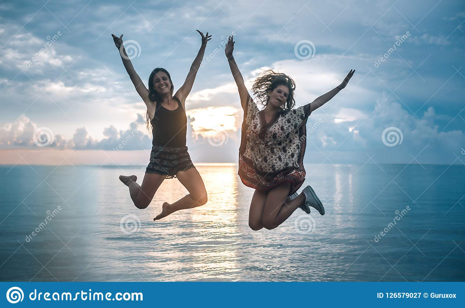 c4bda776a5ab1 Two Happy Girls Jumping At Sunset On Tropical Beach Stock Image ...