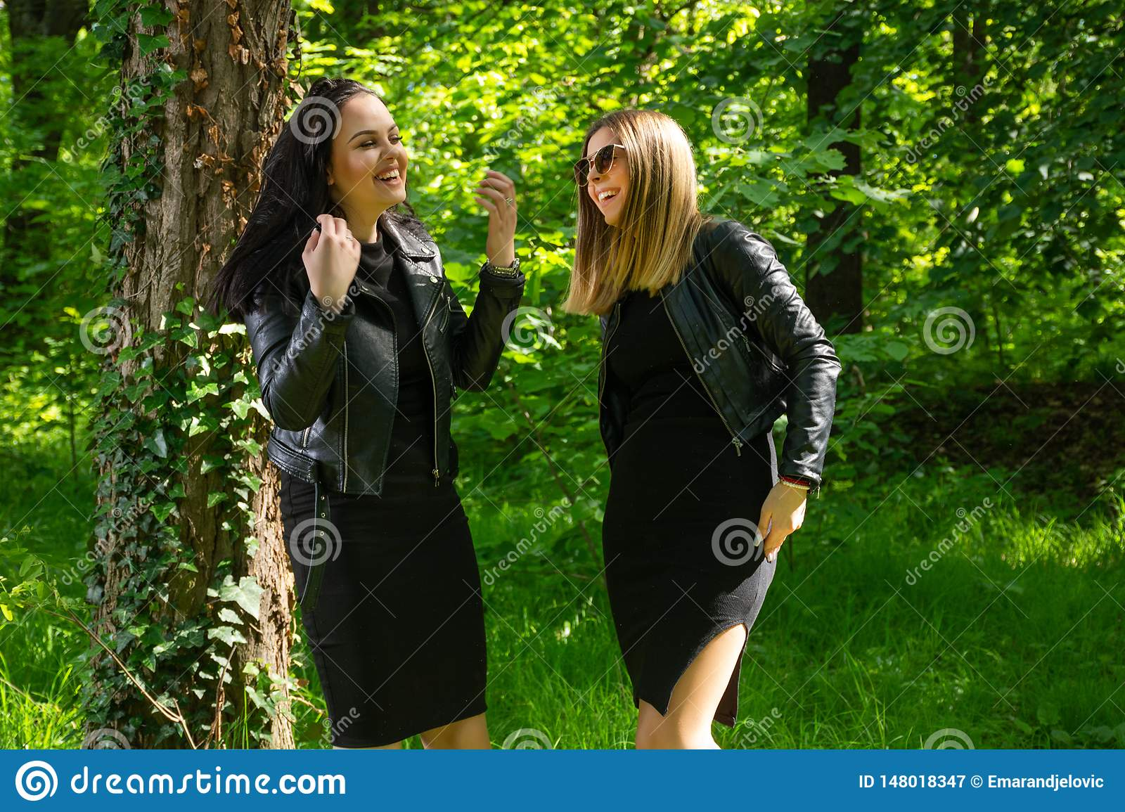 Two happy girls laugh with teeth smile on spring sunny day in the forest