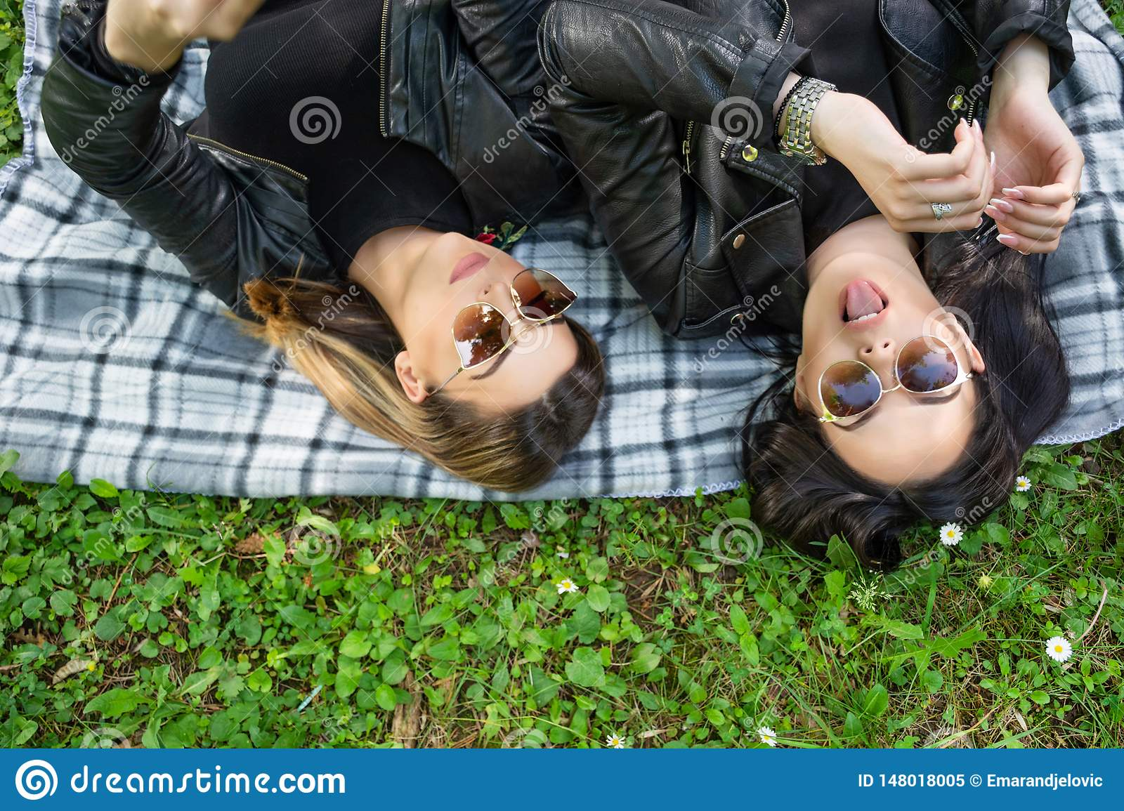 Two happy girls lying down on blanket in a green meadow on a spring day in nature