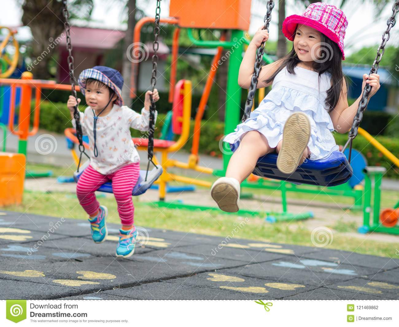 Two Happy little girls playing swing at the playground. Happy, F