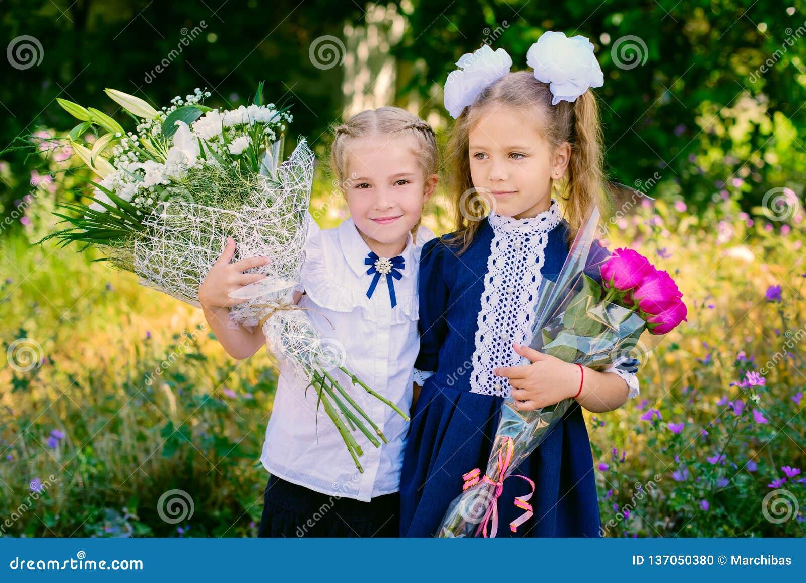 Two happy little schoolgirls with bouquets