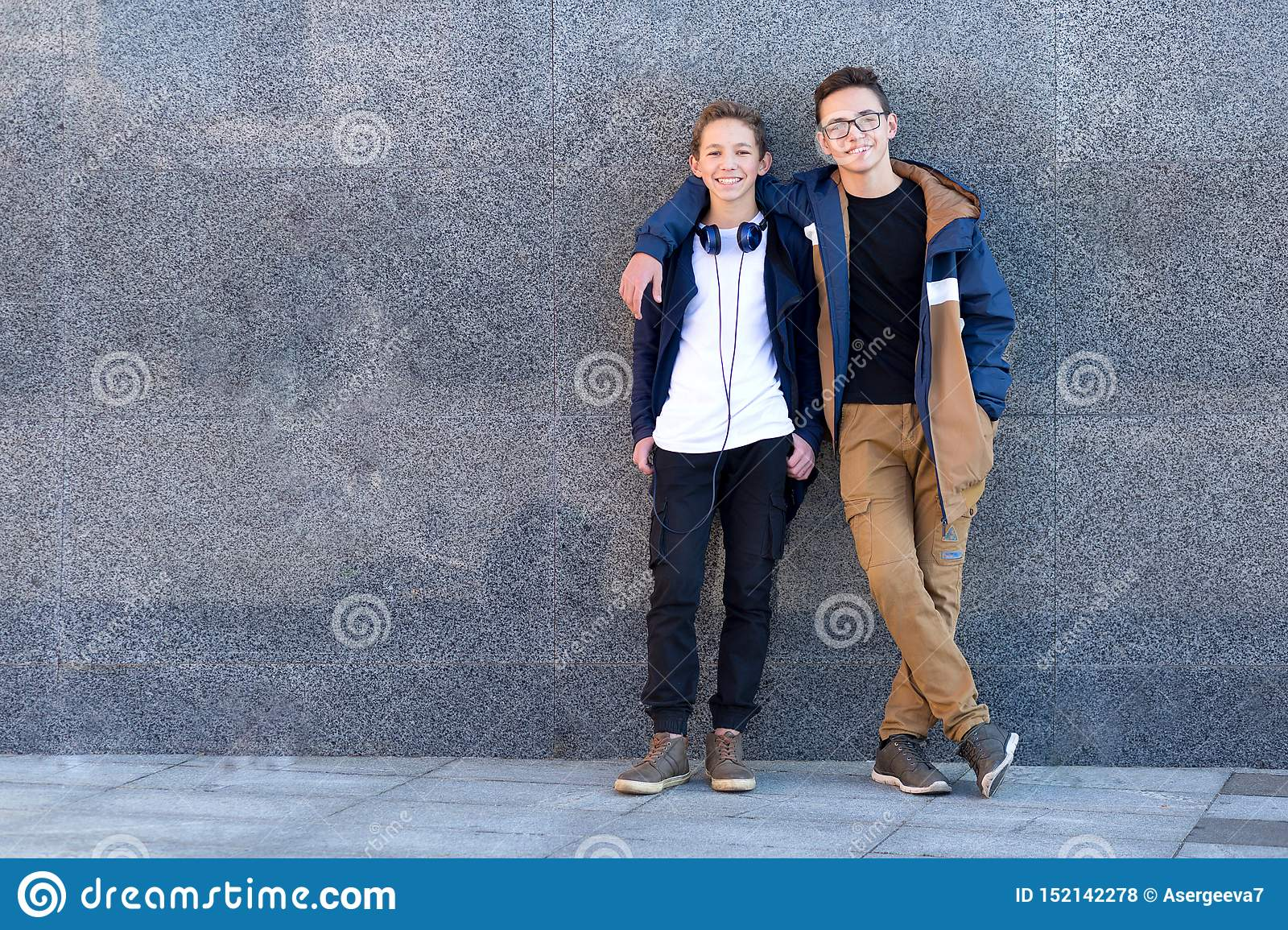Two happy male friends standing together and looking at camera