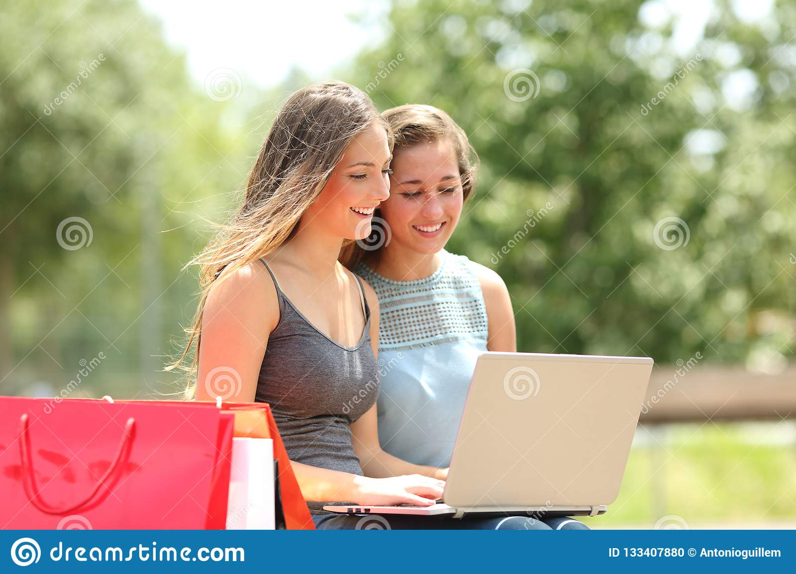 Two shoppers searching products on a laptop