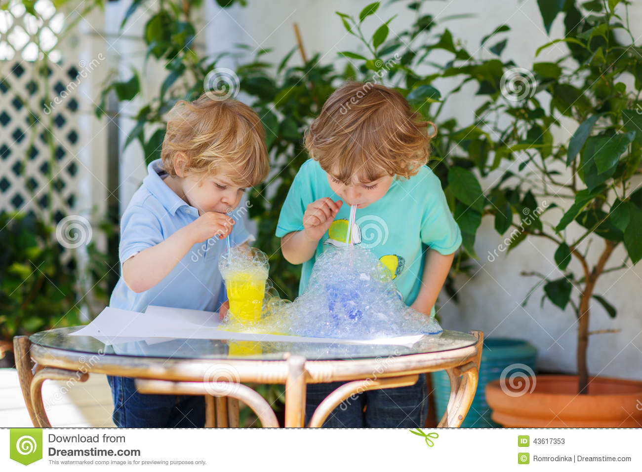 Two happy sibling boys making experiment with colorful bubbles