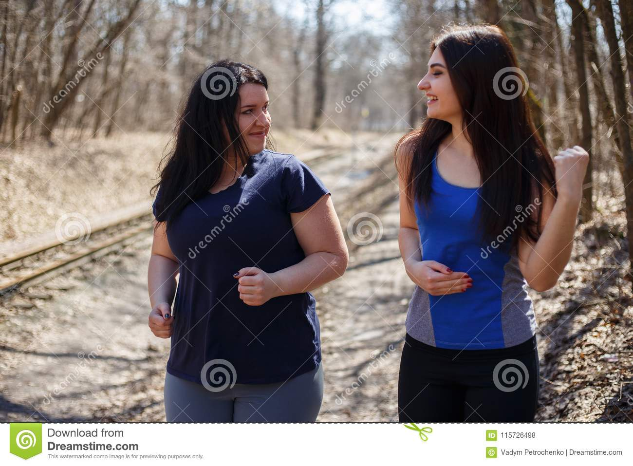 Two happy smiling fit and overweight women friends jogging in th