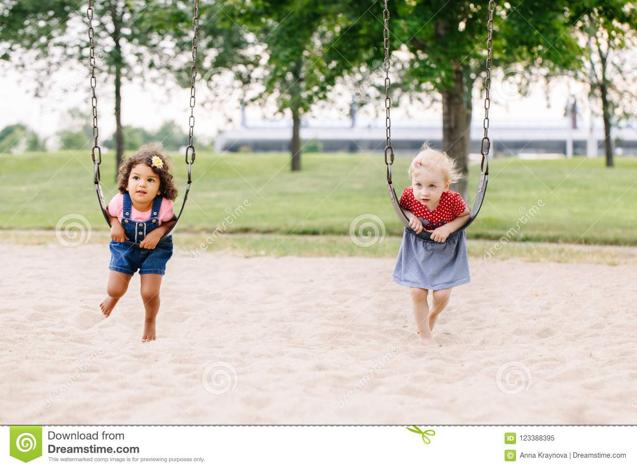 Two happy smiling little toddlers girls friends swinging on swings at playground outside