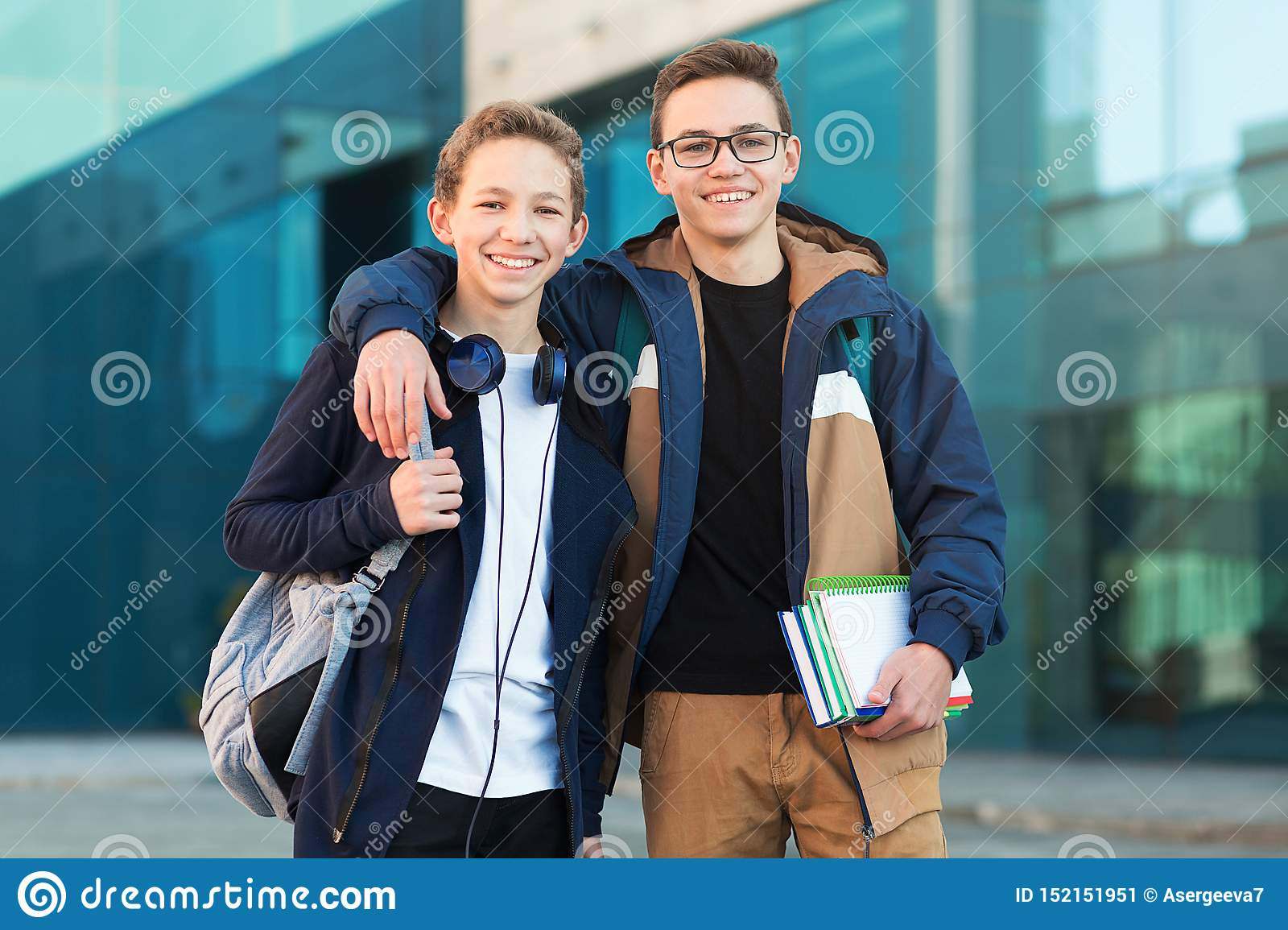 Two happy teenage friends standing together and looking in camera