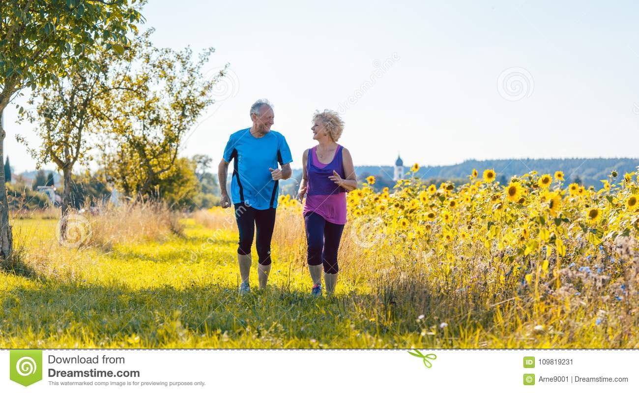 Two healthy senior people jogging on a country road in summer