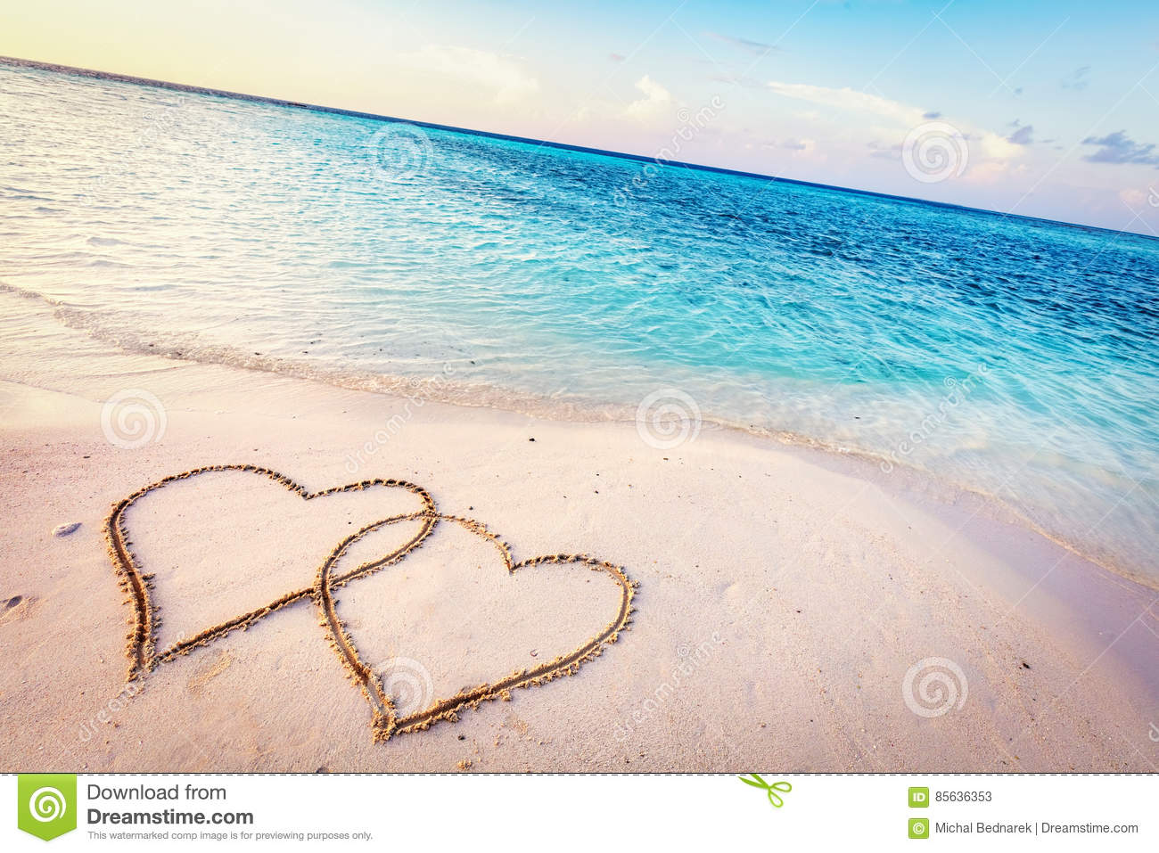 Two Hearts Drawn On Sand Of A Tropical Beach At Sunset