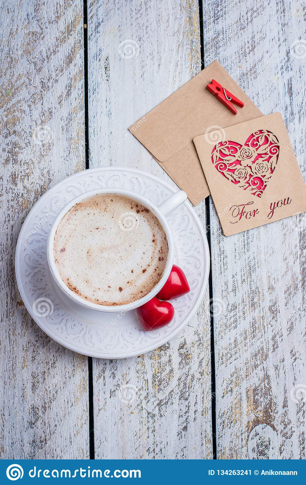 Two hearts, gift card and cup of coffee on white wooden table background. Morning greeting. Valentine`s day concept, top view,