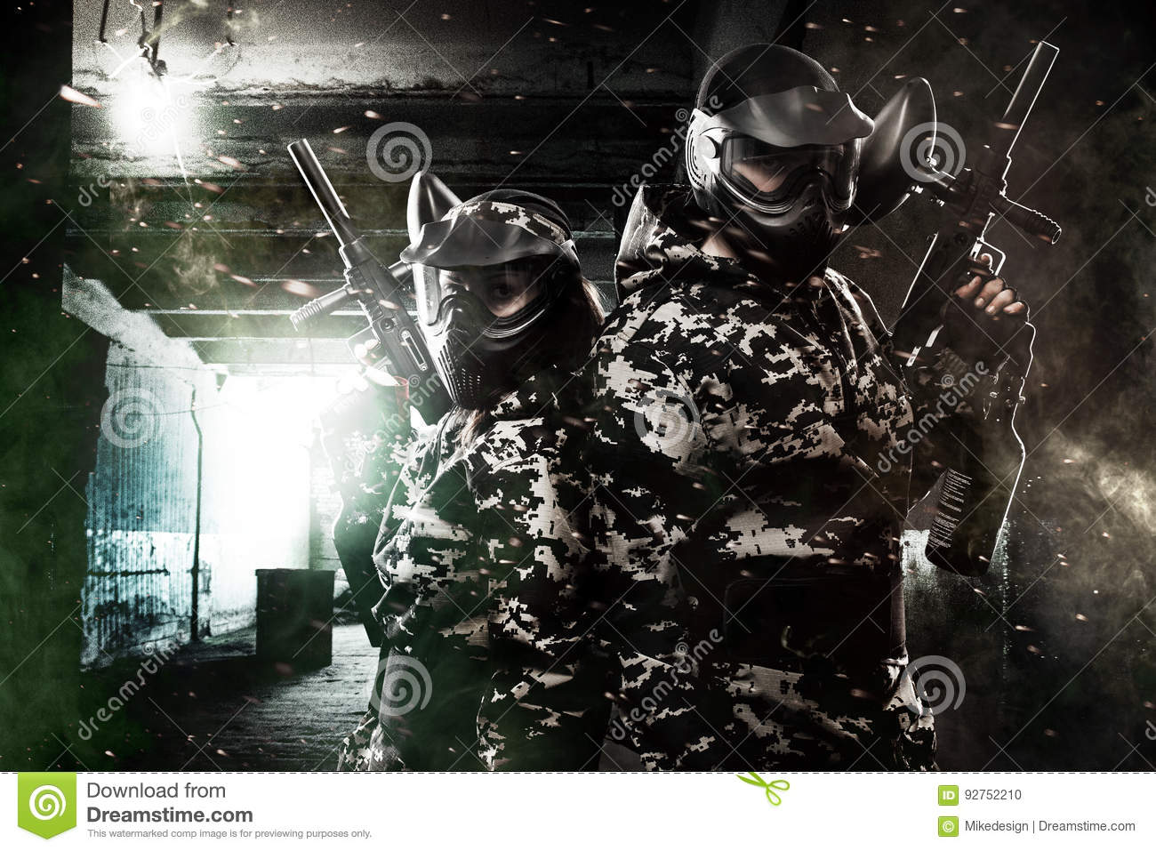 Two heavily armed masked paintball soldier on post apocalyptic background. Ad concept.