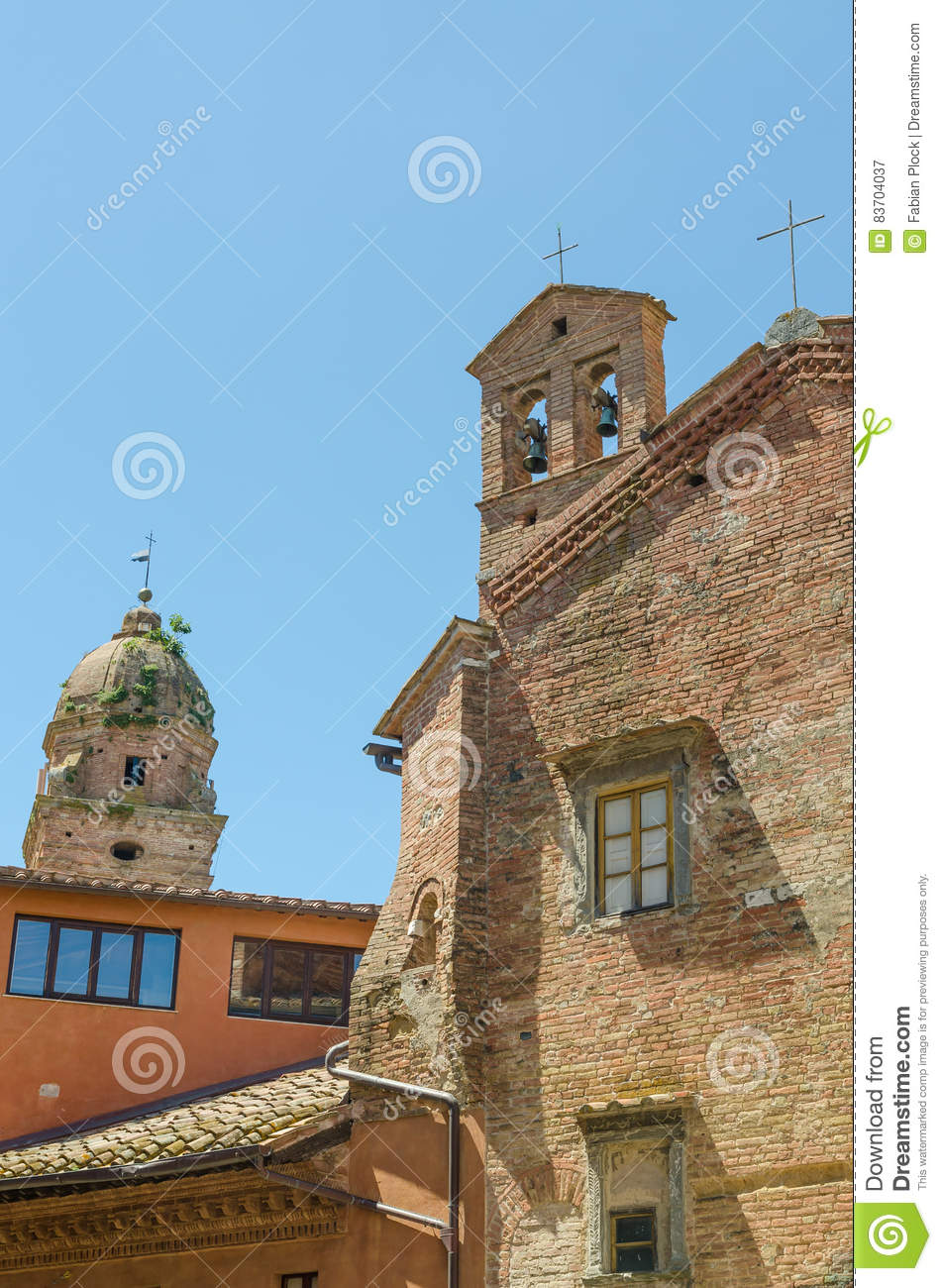 Two Historic Brick Churches With Towers In Contrast To More Modern Orange House In Siena, Italy, Europe Stock Photo