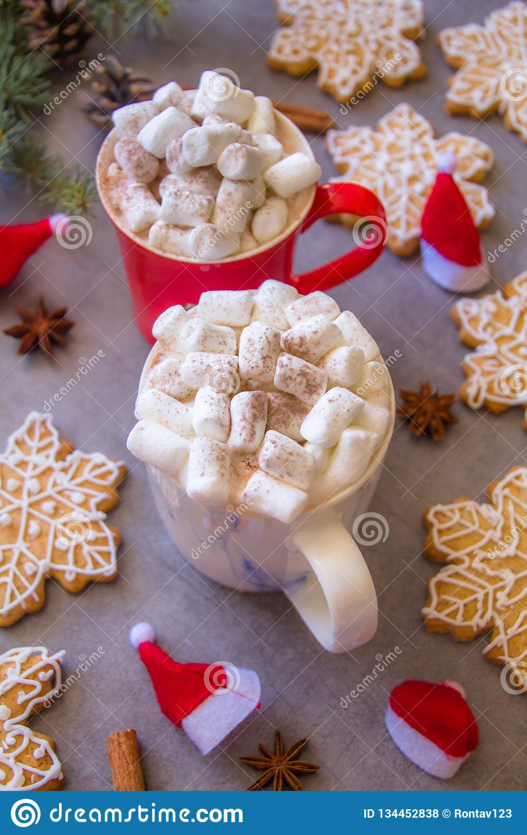 Two hot chocolate cups and marshmallows , against grey background & Christmas composition with Snowflake gingerbread cookies