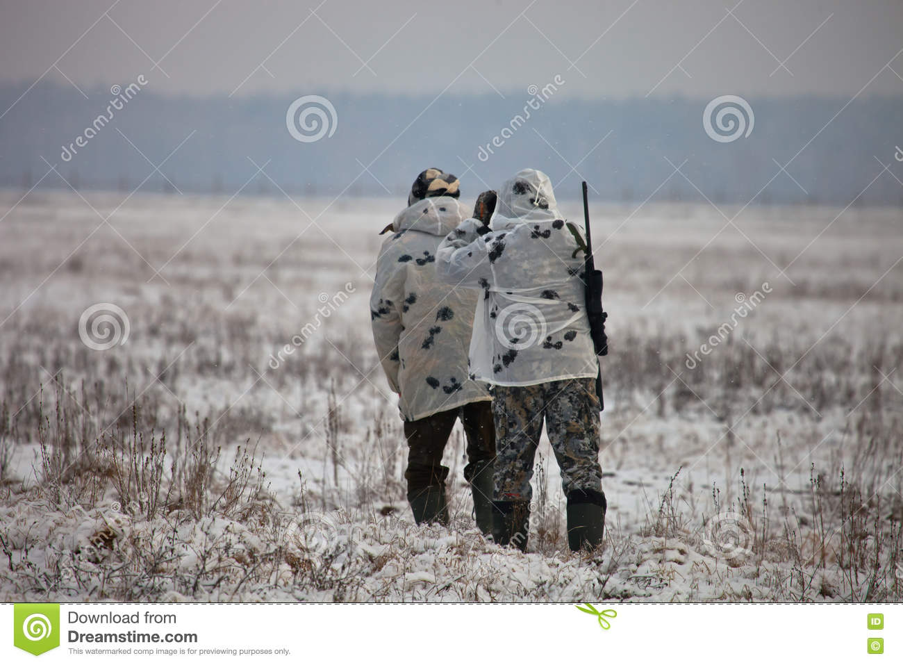 Two hunters in winter camouflage to sneak up on the field