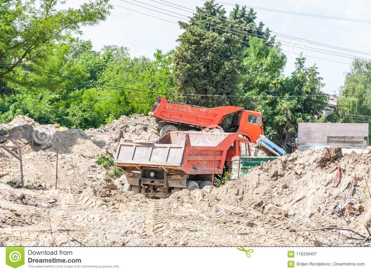 Two industrial tipper trucks on the earth or ground excavation site ready to be loaded