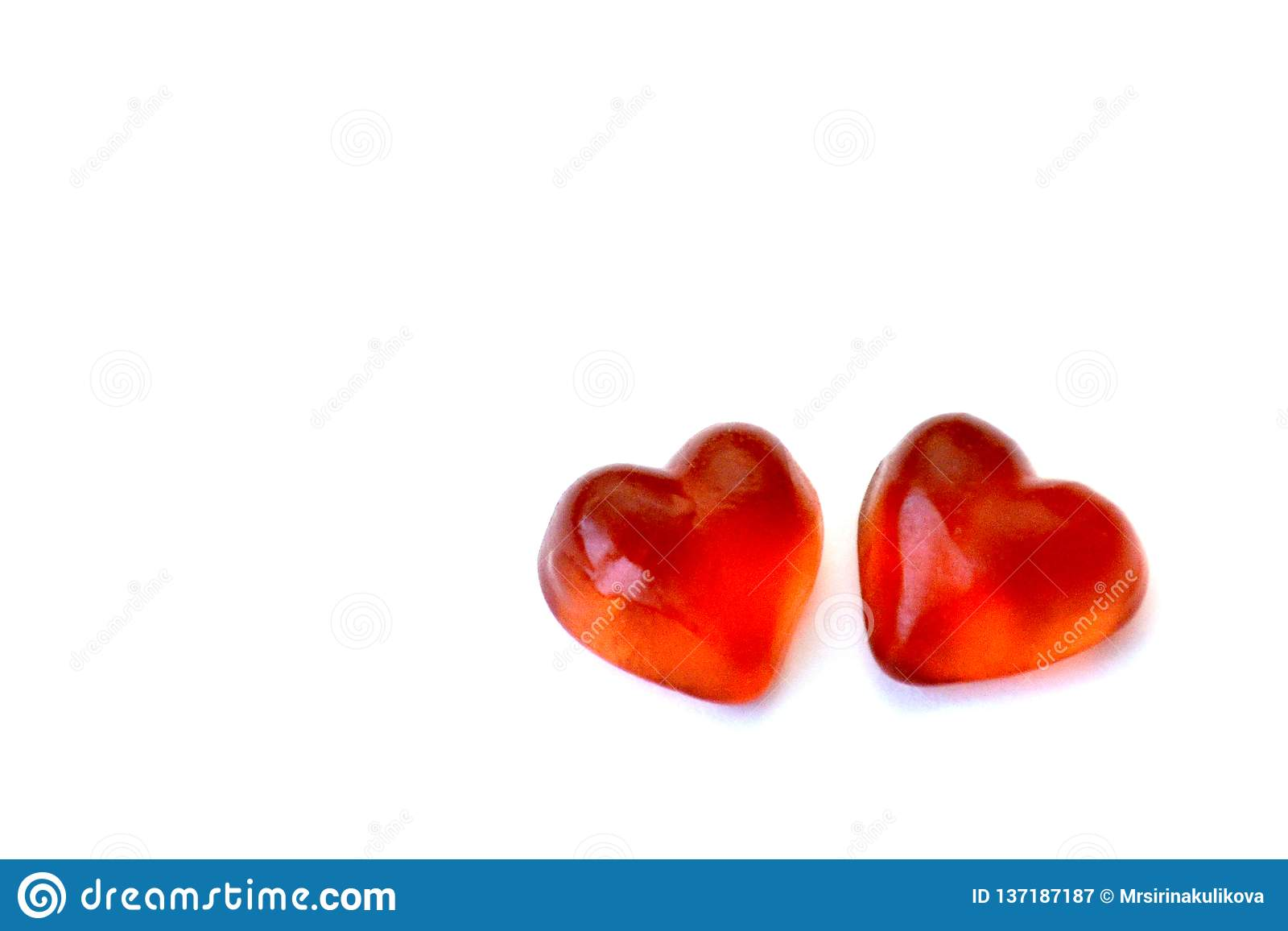 Two jelly candies in the form of red hearts on a white background with copy space. The concept of love and Valentine Day