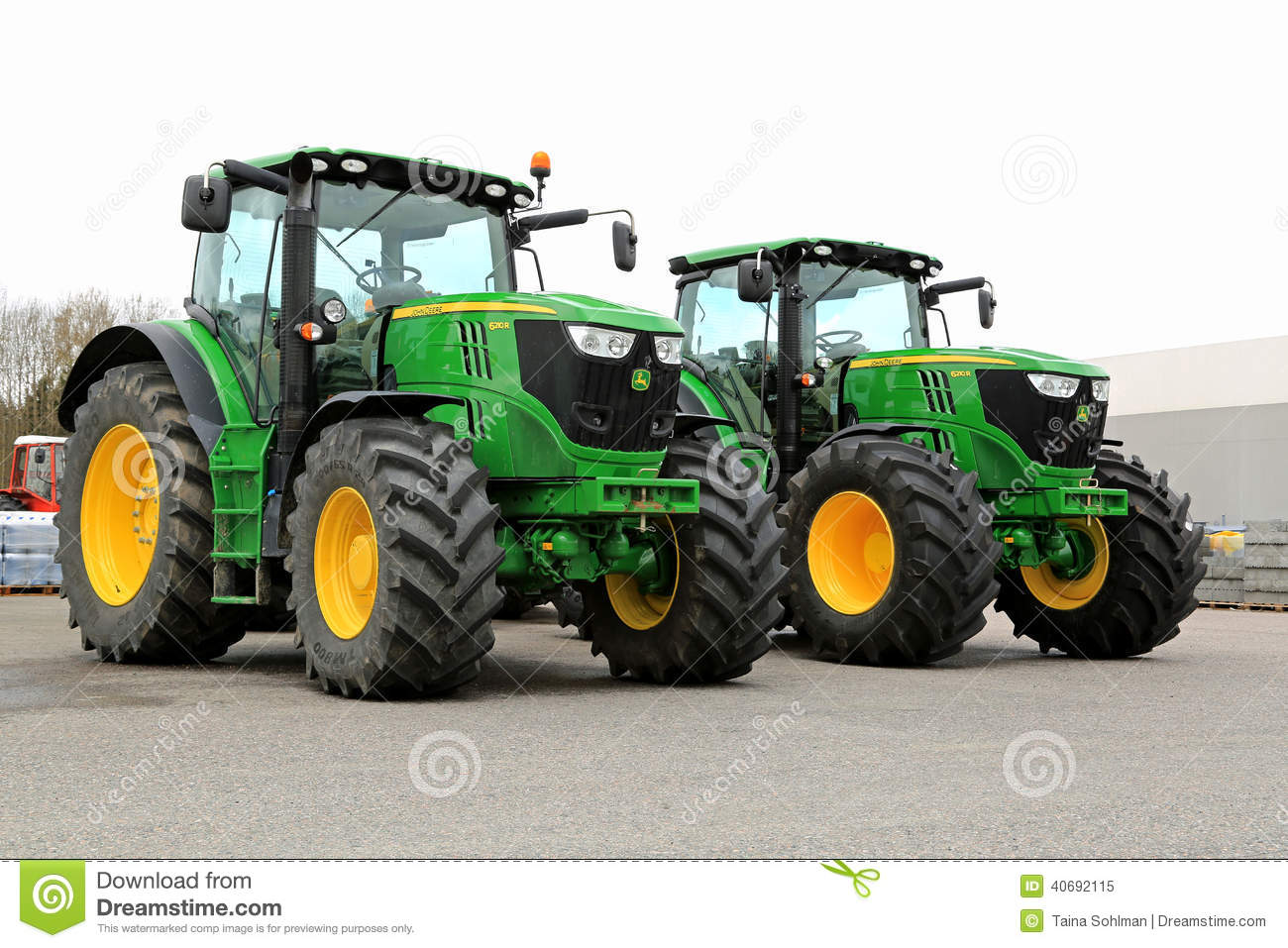 Two John Deere 6210R Agricultural Tractors on a Yard.