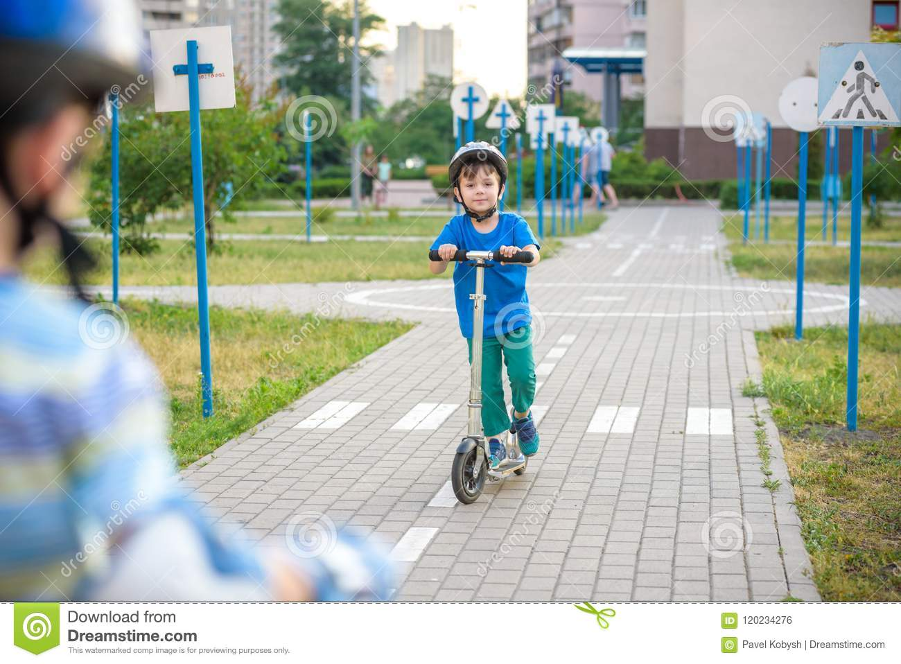 Two Kid Boy On Roller Skates And His Sibling Brother On Scooter