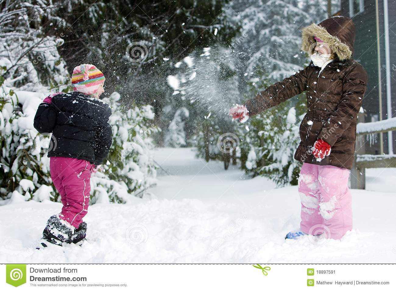 Two young children throwing snowballs at each other during a winter ...