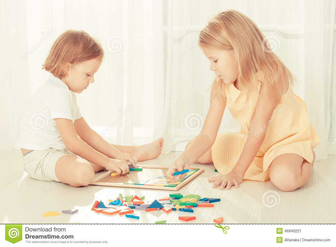 Two kids playing with wooden mosaic in their room