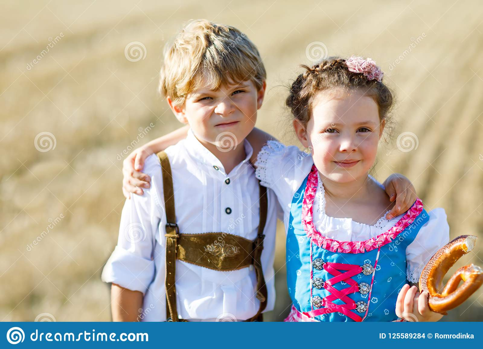 Two kids in traditional Bavarian costumes in wheat field. German children eating bread and pretzel during Oktoberfest