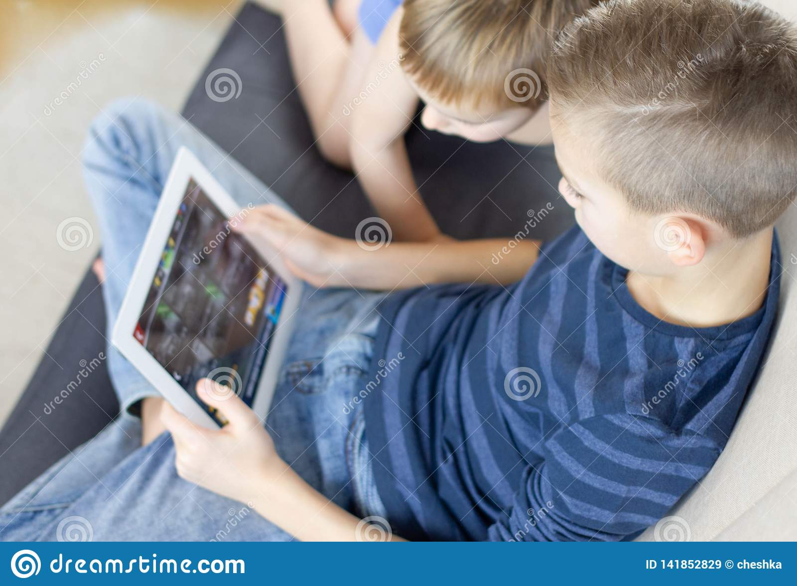 Two kids using tablet at home. Brothers with tablet computer in light room. Boys playing games on tablet pc, emotions.