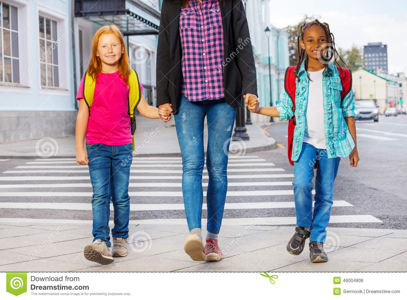 kids with women safely walking over the crossing on the street holding ...