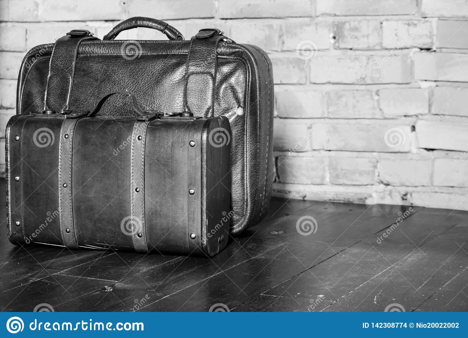 Two leather suitcases on brick wall black and white. Retro baggage design monochrome. Travel and tourism concept.