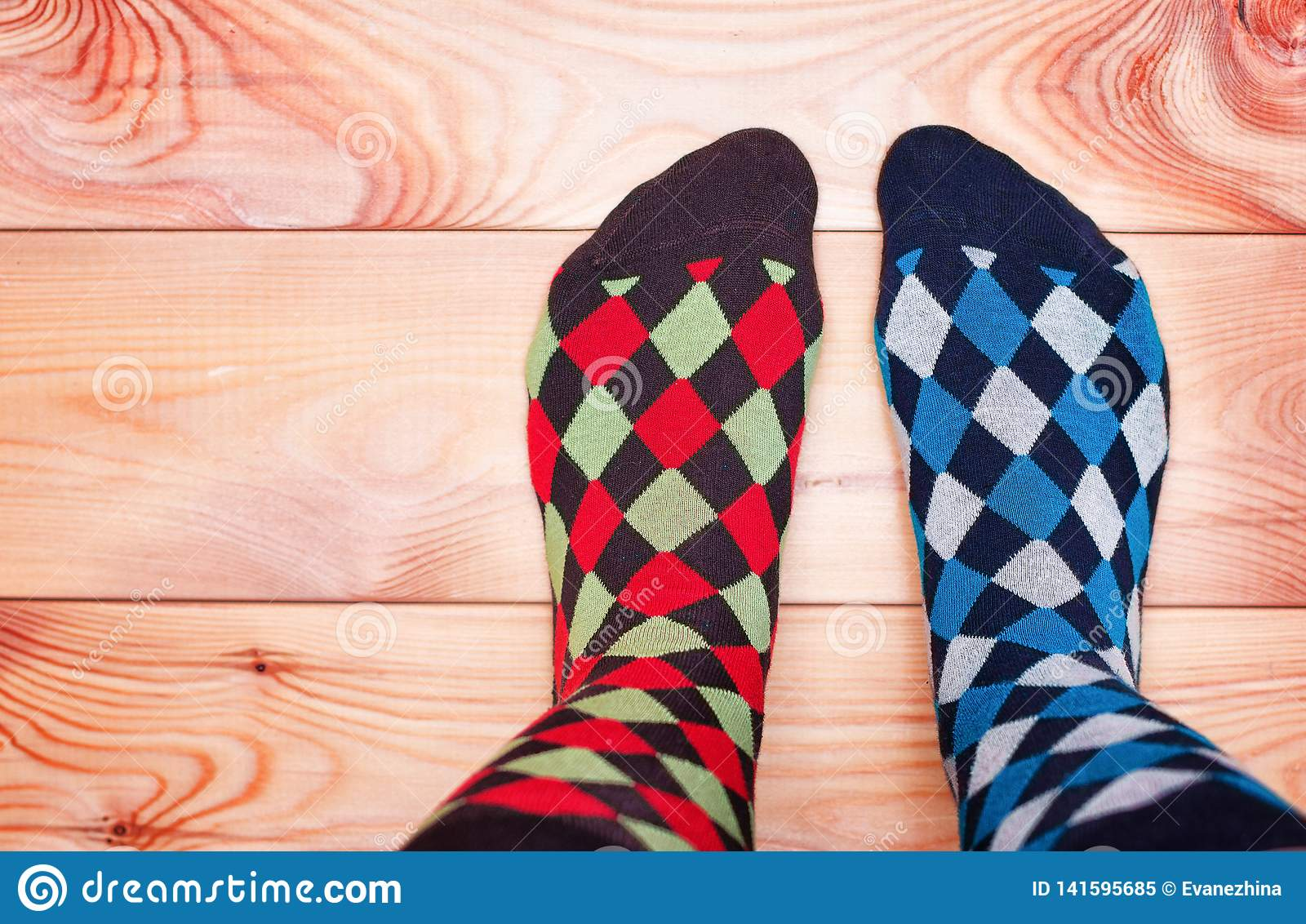 Two legs in different motley socks on a wooden floor