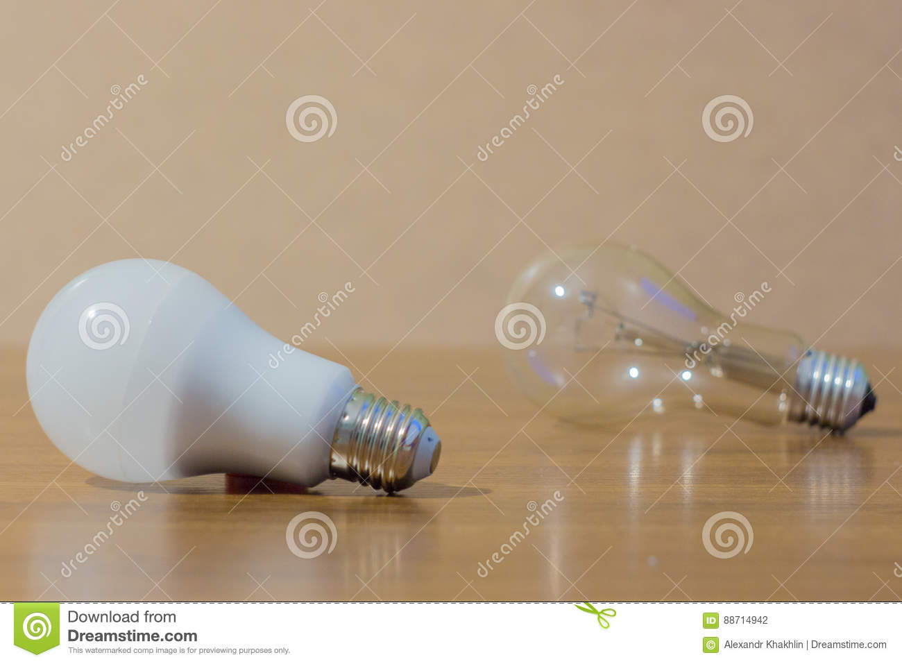 Two light bulbs. LED white and ordinary lamp on wooden background