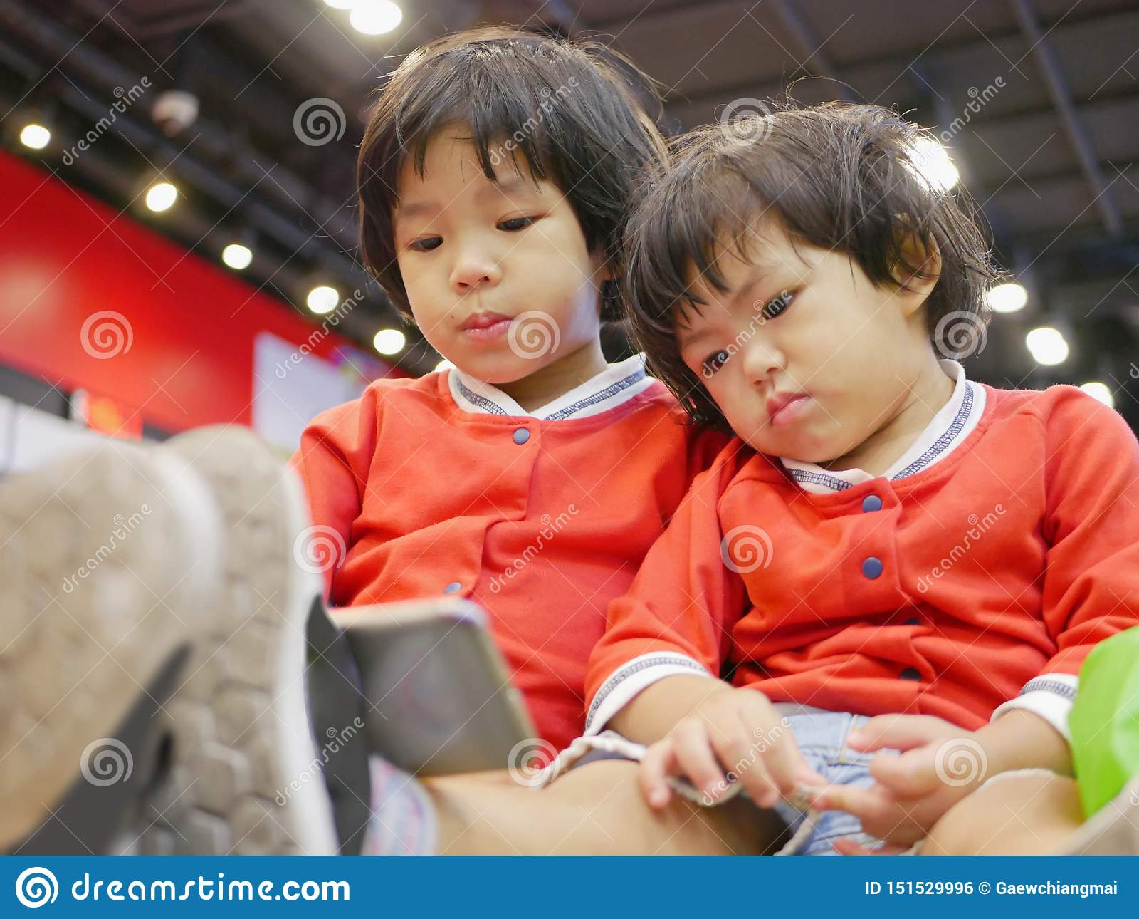 Two little Asian baby girl, sisters, sitting and watching a smartphone together, while waiting for her mother to do some errands